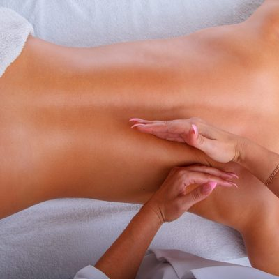 Female enjoing relaxing back massage in cosmetology spa centre.